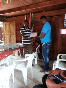 Wesley Rozenhout voorzitter SPBO overhandigt een copie van zijn diploma aan het grootopperhoofd van de Aucanders
